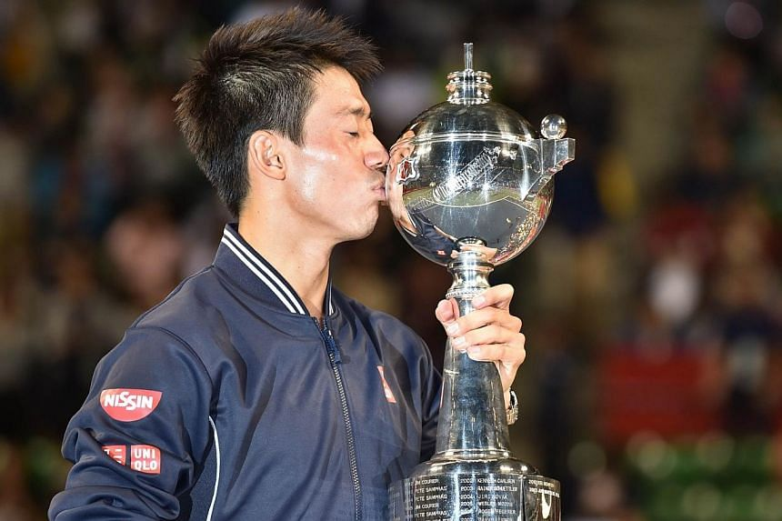 Kei Nishikori of Japan kisses the trophy during the awards ceremony after the men's singles final against Milos Raonic of Canada at the Japan Open tennis tournament in Tokyo on Oct 5, 2014. Local hero Nishikori beat Raonic 7-6 (7-5), 4-6, 6-4. -