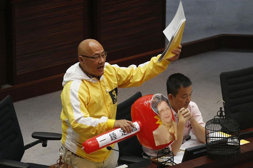 Pro-democracy lawmaker Albert Chan shouts while holding an electoral reforms consultation report and a plastic hammer featuring a portrait of Hong Kong Chief Secretary Carrie Lam, during a meeting with Lam on proposing electoral reforms at the Legisl