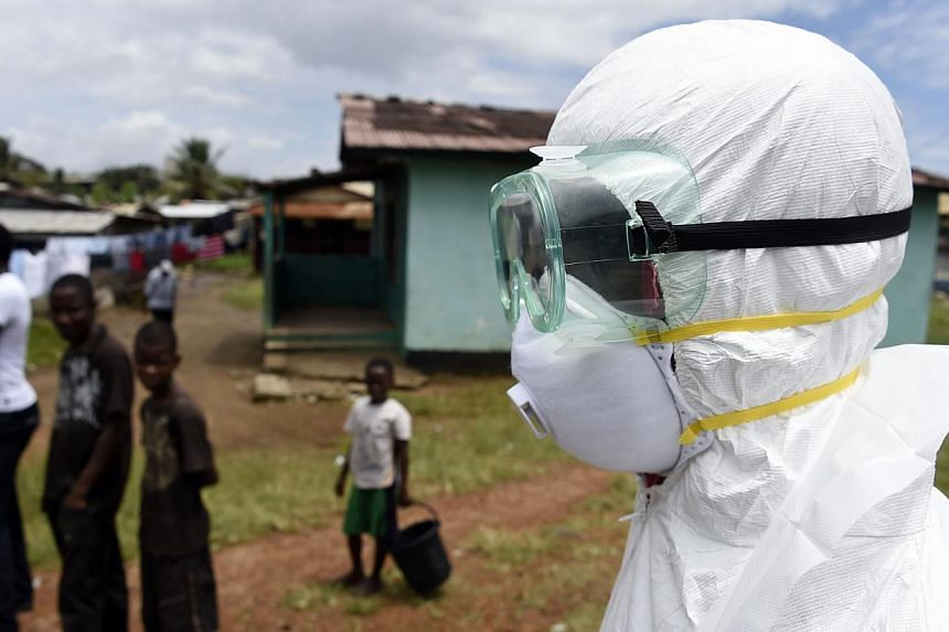 Children look on as a Red Cross worker makes his way to collect a body of a person suspected of dying from the Ebola virus, from a house in the Center Street neighborhood of the Liberian capital Monrovia, on Oct 4, 2014. Aid workers and health-care o