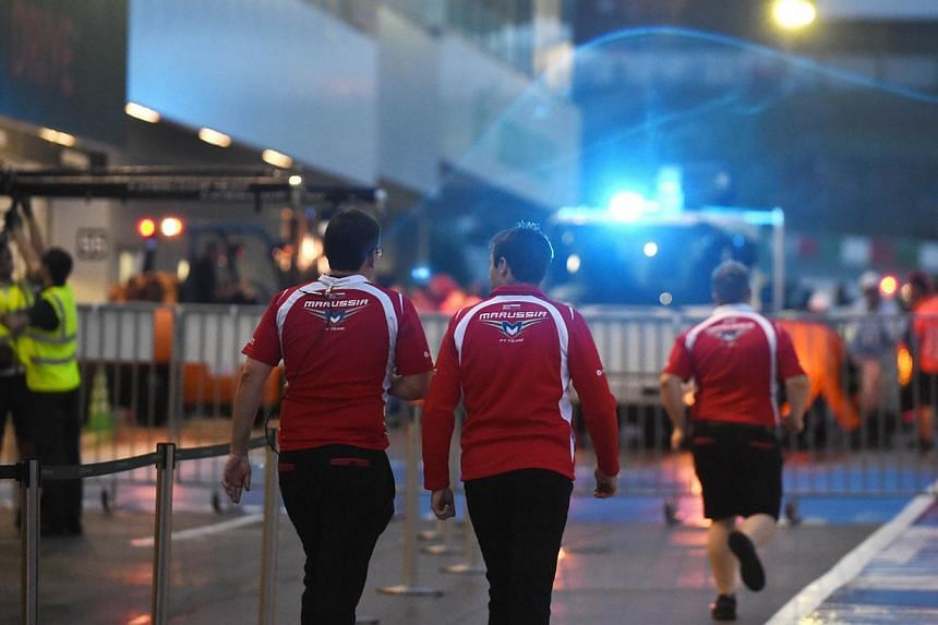 Marussia team officials walk towards the parc ferme as the race car of Jules Bianchi of France returns to the pit after a crash during the Formula One Japanese Grand Prix in Suzuka on Oct 5, 2014.The wet Japanese Formula One Grand Prix on Sunda