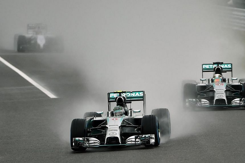 Mercedes driver Nico Rosberg of Germany (centre) leads Mercedes driver Lewis Hamilton of Britain (right) after the safety car entered the pit to start the Formula One Japanese Grand Prix in Suzuka on Oct 5, 2014. -- PHOTO: AFP