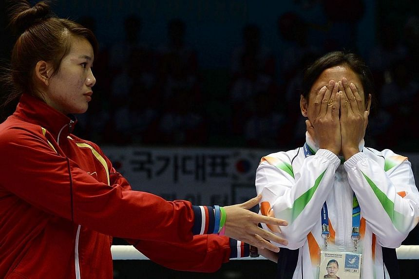 This file photo taken on Oct 1, 2014, shows bronze medallist Luu Thi Duyen (left) of Vietnam urging India's Laishram Sarita Devi to go on to the podium after she decided to refuse to accept her bronze medal during the women's lightweight (57-60kg) bo