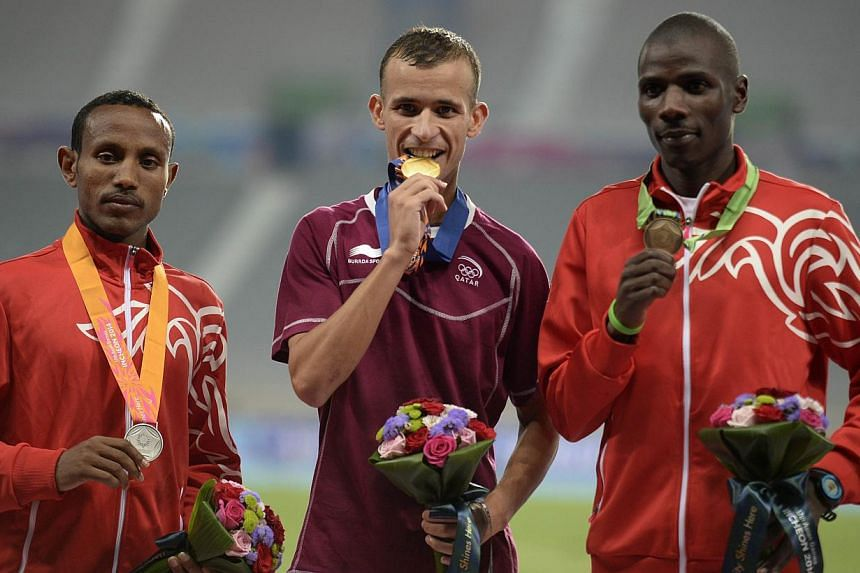 (From left) Silver medallist Alemu Bekele Gebre of Bahrain, gold medallist Mohamad Al Garni of Qatar and bronze medallist Albert Kibichii Rop of Bahrain pose with their medals on the podium during the victory ceremony for the men's 5,000m athletics e