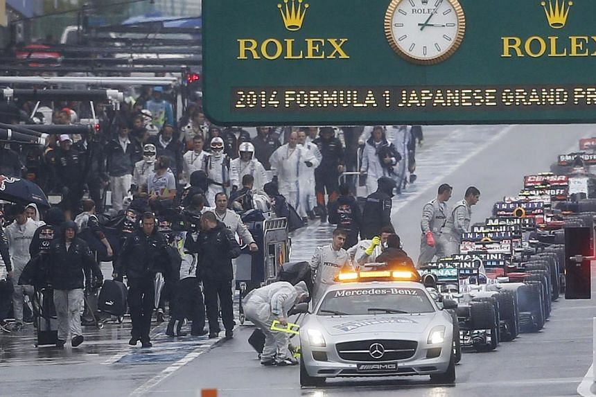 Cars line up behind the safety car in the pit lane as the race is suspended due to rain conditions during the Japanese F1 Grand Prix at the Suzuka Circuit on Oct 5, 2014. -- PHOTO: REUTERS