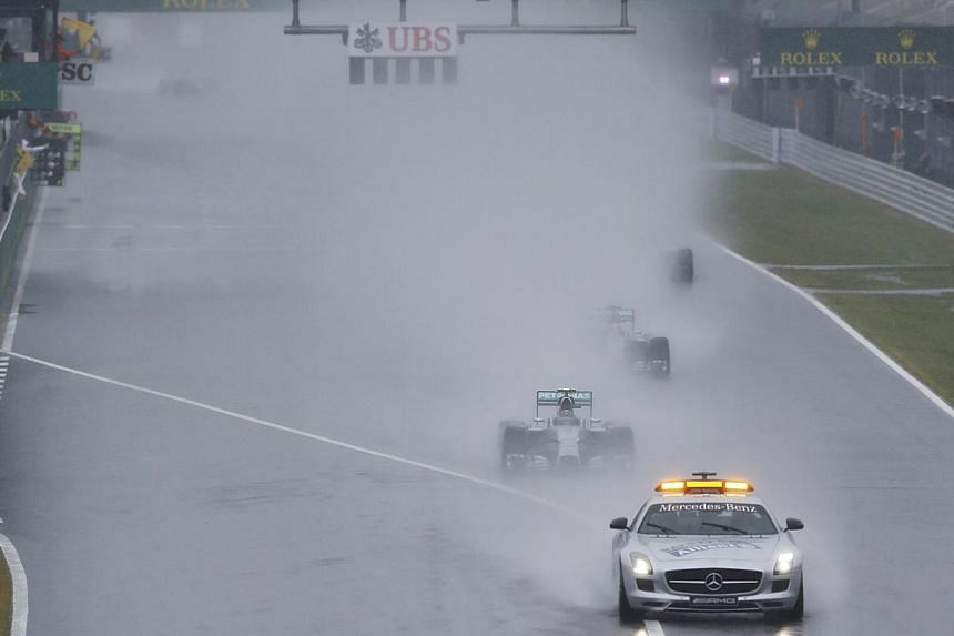 Mercedes Formula One driver Nico Rosberg of Germany leads team mate Lewis Hamilton of Britain behind a safety car as they start the first lap of the rain-affected Japanese F1 Grand Prix at the Suzuka Circuit on Oct 5, 2014. -- PHOTO: REUTERS