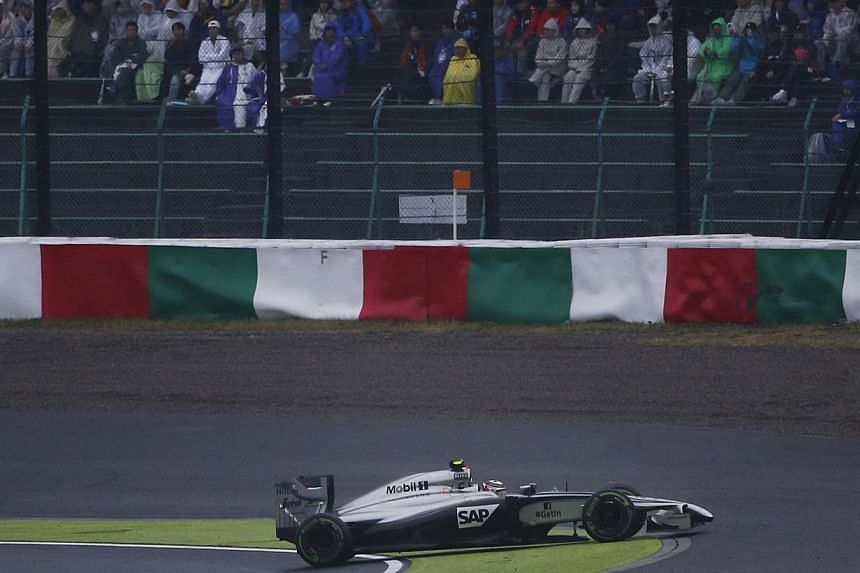 McLaren Formula One driver Kevin Magnussen of Denmark spins unto the grass during the Japanese F1 Grand Prix at the Suzuka Circuit on Oct 5, 2014. -- PHOTO: REUTERS