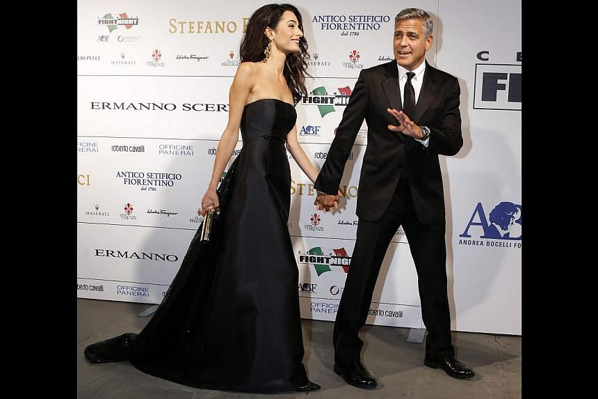Wearing a Dolce & Gabbana gown to Celebrity Fight Night in Florence last month (above): A classic, black strapless gown lets the lawyer's beauty shine through and statement gold earrings draw attention to her face. It is an appropriately elegant,