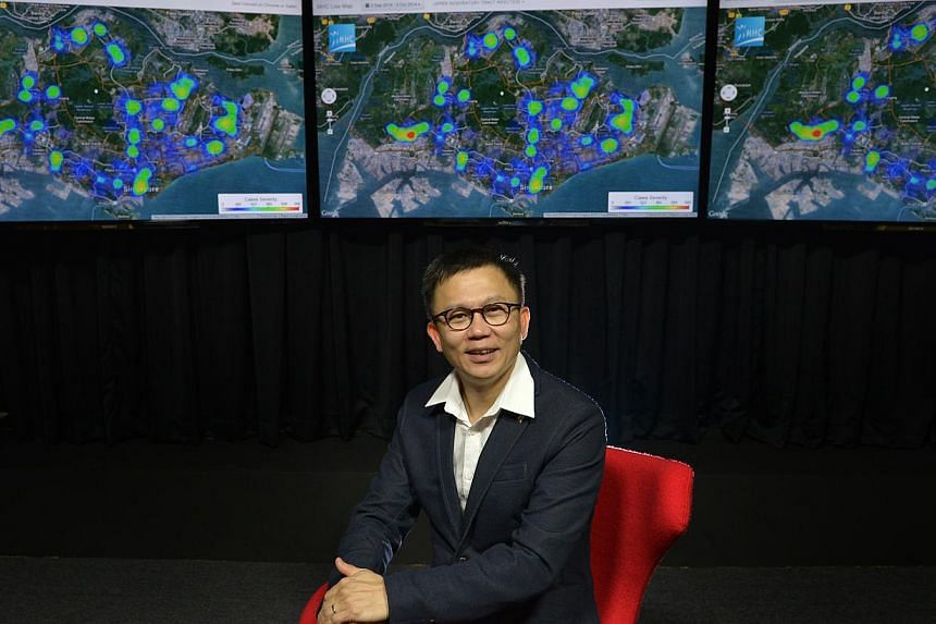Dr Low Lee Yong, founder of Make Health Connect (MHC), with a projection of the live disease map showing hotspots of illnesses doctors dealt with.