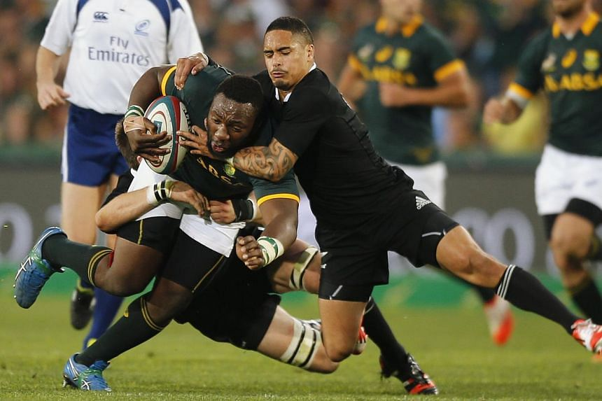 New Zealand's Aaron Smith (right) tackles South Africa's Tendai Mtawarira during their Rugby Championship match at Ellis Park stadium in Johannesburg Oct 4, 2014. -- PHOTO: REUTERS