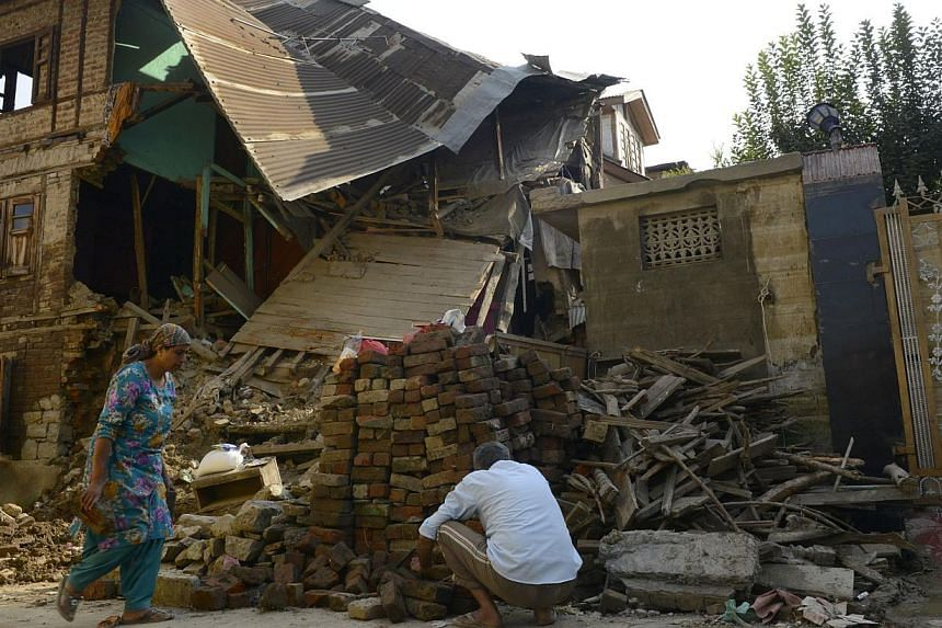 A Kashmiri man works at his flood-damaged house in Srinagar on Oct 3, 2014.Pakistan on Saturday barred activists from taking relief goods intended for flood victims to the border of Indian-controlled Kashmir, where delays in aid have created wi