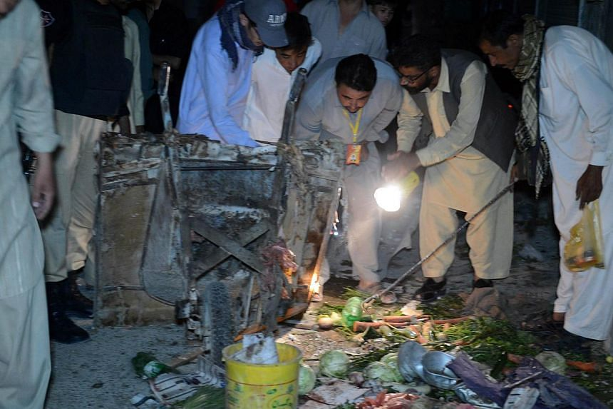 Pakistani security officials and Shi'ite Muslims inspect the site of suicide bomb attack in Quetta on Oct 4, 2014. At least five people were killed and 25 others wounded when a suicide bomber blew himself up on Oct 4, 2014 in a minority Shi'ite colon