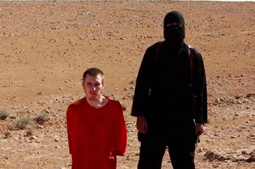 A masked man stands next to a kneeling man identified as US citizen Peter Edward Kassig, in this still image taken from a video released by Islamic State militants in Iraq and Syria, on Oct 3, 2014. Kassig's parentsissued a video plea for their