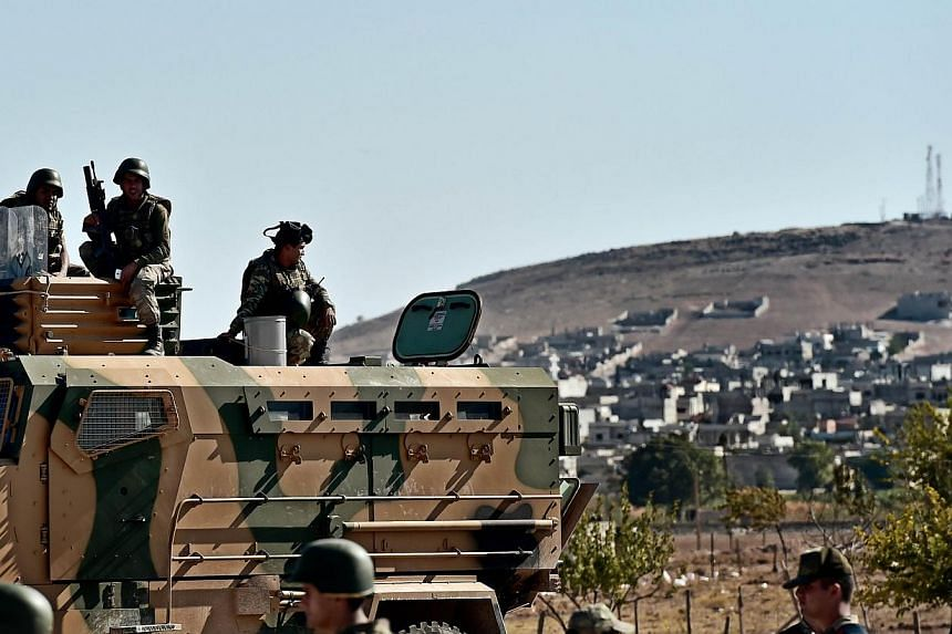 Turkish soldiers stand in front of the Syrian town of Ain al-Arab, known as Kobane by the Kurds, at the Mursitpinar border crossing on the Turkish-Syrian border in the southeastern town of Suruc, Sanliurfa province, on Oct 5, 2014. -- PHOTO: AFP