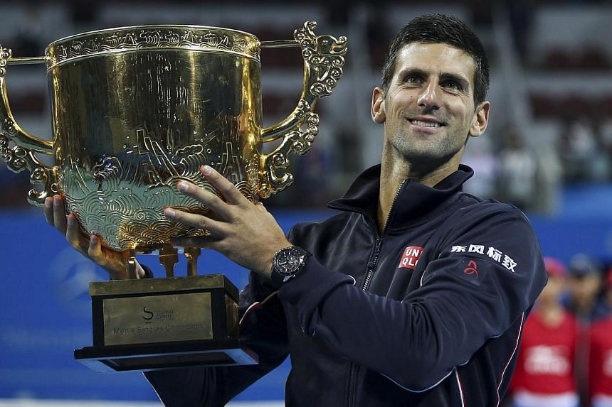 Novak Djokovic of Serbia holds his trophy as he poses for pictures after winning the men's singles final match against Tomas Berdych of the Czech Republic at the China Open tennis tournament in Beijing on Oct 5, 2014. -- PHOTO: REUTERS