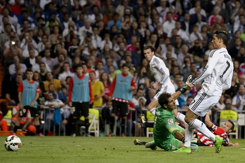 Real Madrid's Portuguese forward Cristiano Ronaldo shoots to score during the Spanish league football match against Athletic Bilbao at the Santiago Bernabeu stadium in Madrid on Oct 5, 2014. -- PHOTO: AFP