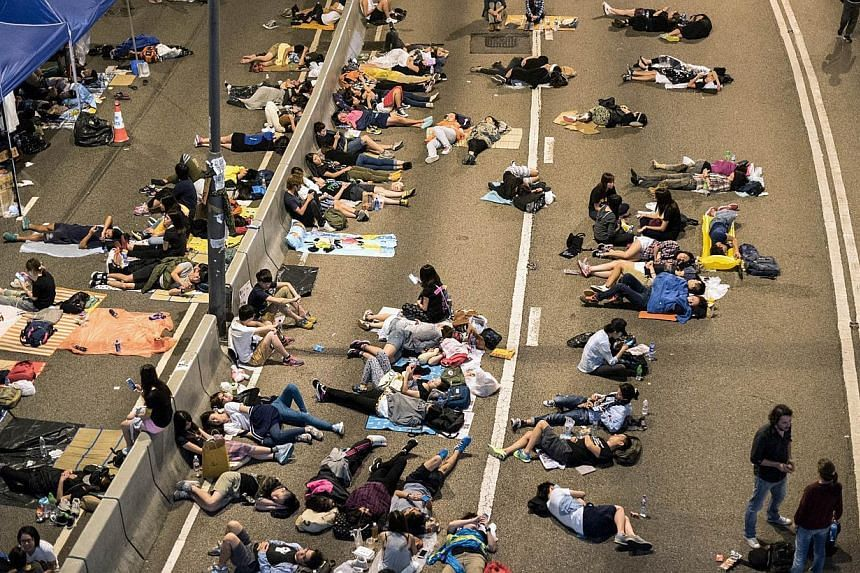 Pro-democracy protesters rest on a highway next to the central government offices in Hong Kong on Oct 6, 2014. -- PHOTO: AFP