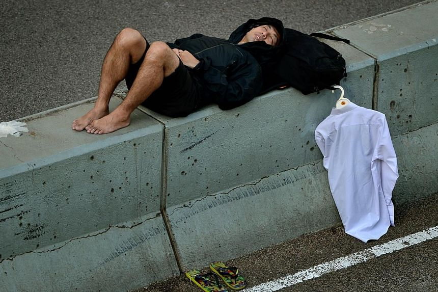 A man sleeping on a road barrier in Admiralty district in Hong Kong on Oct 6, 2014. -- ST PHOTO: KUA CHEE SIONG