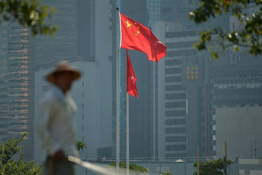 A man works in a park in front of the flags of China and Hong Kong in Hong Kong on Oct 6, 2014. -- ST PHOTO: KUA CHEE SIONG