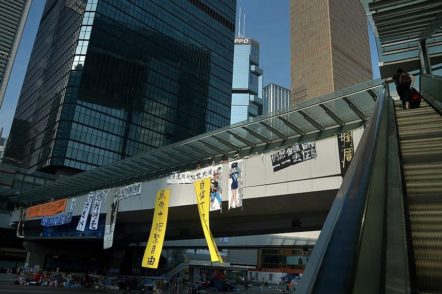 Banners hang from a bridge in Hong Kong as office workers try to get to work amid the diversions due to blockades by the protesters at the Central Government offices in Admiralty district on Oct 6, 2014. -- ST PHOTO: KUA CHEE SIONG