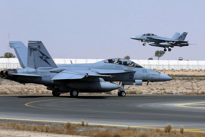 A Royal Australian Air Force (RAAF) F/A-18F Super Hornet takes off as another taxis along the runway as they start their first combat mission over Iraq in this picture released by the Australian Defence Force on Oct 6, 2014.Australian fighter j