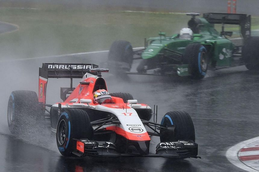 Marussia driver Jules Bianchi (front) of France leads Caterham driver Kamui Kobayashi of Japan at the Formula One Japanese Grand Prix in Suzuka on Oct 5, 2014. -- PHOTO: AFP
