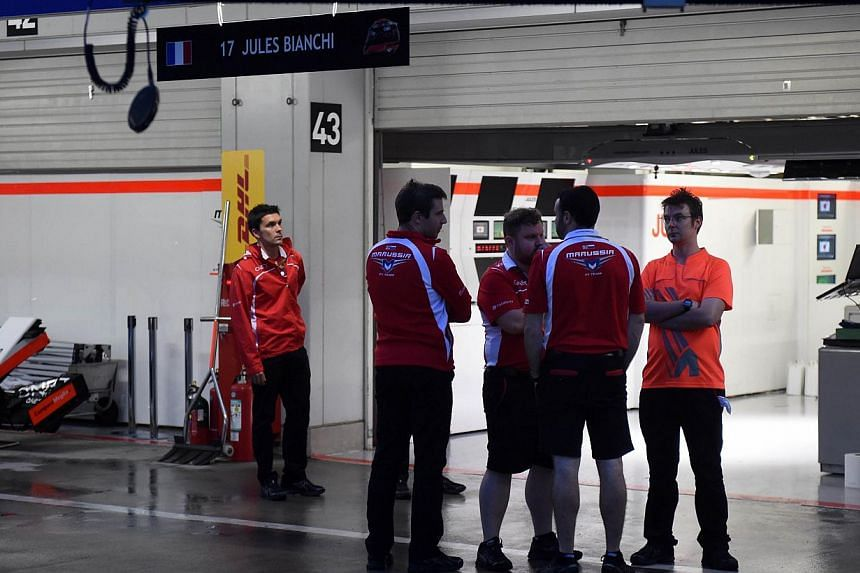 Marussia team officers stand outside the pit after their driver Jules Bianchi of France crashed and was hosptalised. -- PHOTO: AFP