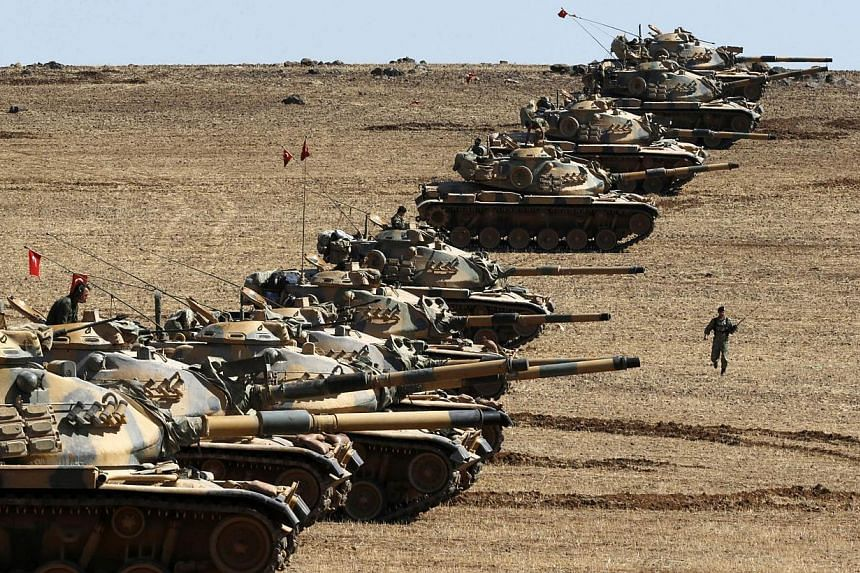 Turkish army tanks take up position on the Turkish-Syrian border near the south-eastern town of Suruc in Sanliurfa province Oct 6, 2014.The fight against the Islamic State in Iraq and Syria (ISIS) group will be difficult and could last decades