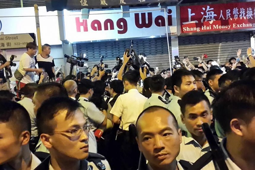 Hong Kong police with batons drawn trying to keep the agitated pro-democracy protesters in Mong Kok under control on Sunday morning (Oct 05, 2014). -- COPYRIGHT: TAN HUI YEE.