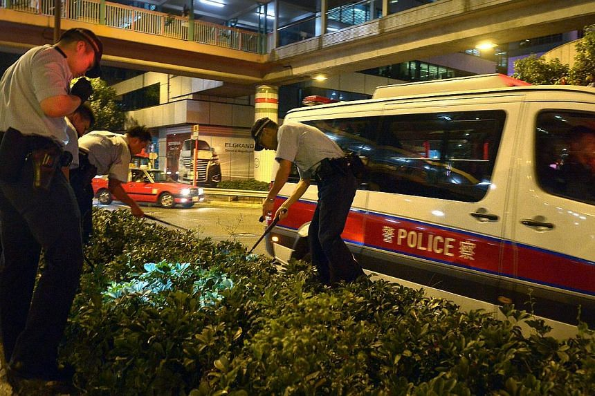 Police search for weapons, after receiving a tip-off that a bag was found with long knives inside along Gloucester Road, which leads to Harcourt Road, where the main protest site is located at 1am on Oct 6, 2014. -- ST PHOTO: KUA CHEE SIONG