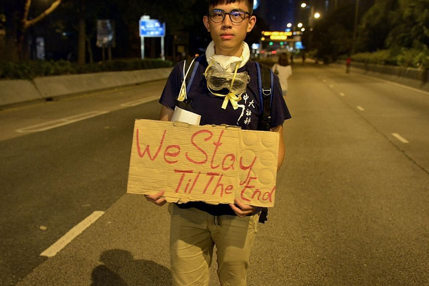 """A protester walking near the main protest site carrying a sign which says, """"We Stay Till The End"""" at 1am on Oct 6, 2014. -- ST PHOTO: KUA CHEE SIONG"""