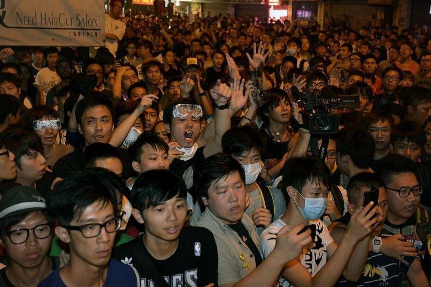 Protesters surround the police demanding for an explanation for letting an anti-protester go after he had beaten a protester in Mong Kok in the wee hours of the morning on Oct 5, 2014. -- ST PHOTO: KUA CHEE SIONG