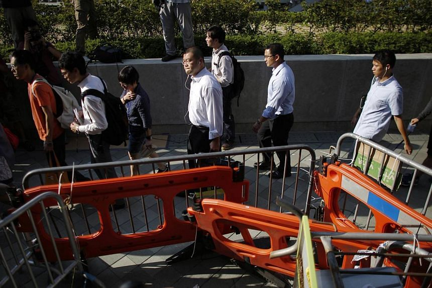 Government employees arrive to work at an area occupied by protesters outside of the government headquarters building in Hong Kong on Oct 6, 2014. -- PHOTO: REUTERS