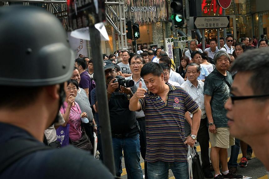 """An anti-protester taunts the protesters at Mong Kok in Kowloon on Oct 6, 2014.A four-day environment symposium which was to gather 11 Nobel laureates in Hong Kong from Wednesday, has been scrapped due to """"sustained disruptions in the city,"""" the"""