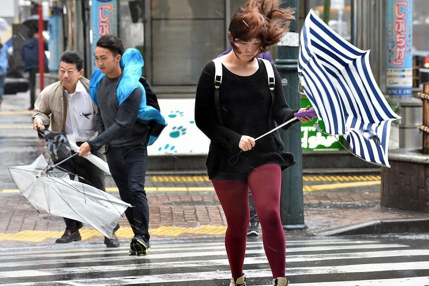 Pedestrians walk against strong wind and rain in Tokyo on Oct 6, 2014. -- PHOTO: AFP