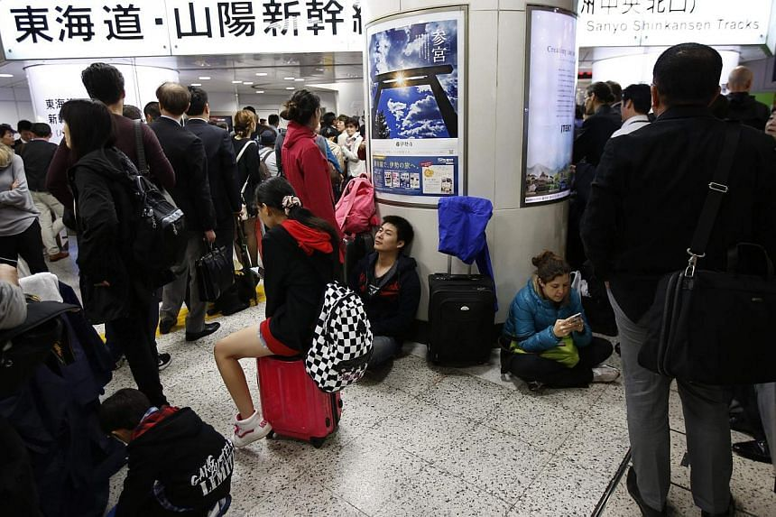 Passengers wait for resumption of bullet train services after they were suspended due to strong winds and heavy rain caused by Typhoon Phanfone, at Tokyo Station on Oct 6, 2014. -- PHOTO: REUTERS