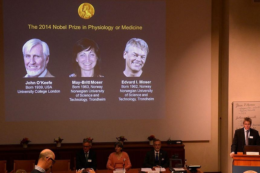 A giant screen displays the image of British-American researcher John O'Keefe and Norwegian duo May-Britt Moser and Edvard I Moser at a press conference of the Nobel Committee to announce the winner of the 2014 Nobel Medicine Prize on Oct 6, 2014 at