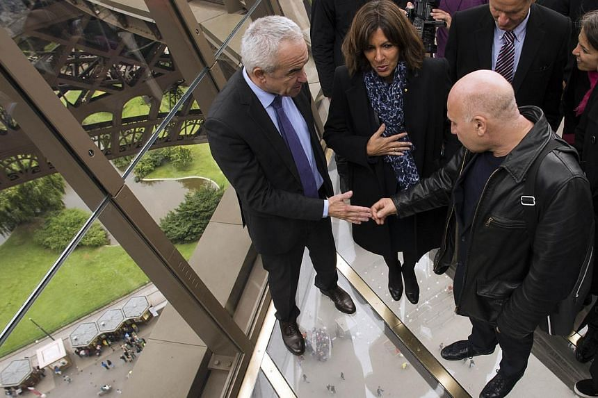 Paris mayor Anne Hidalgo (centre) and the glass floor area's architect Alain Moatti (right) at its inauguration on Oct 6, 2014. -- PHOTO: AFP