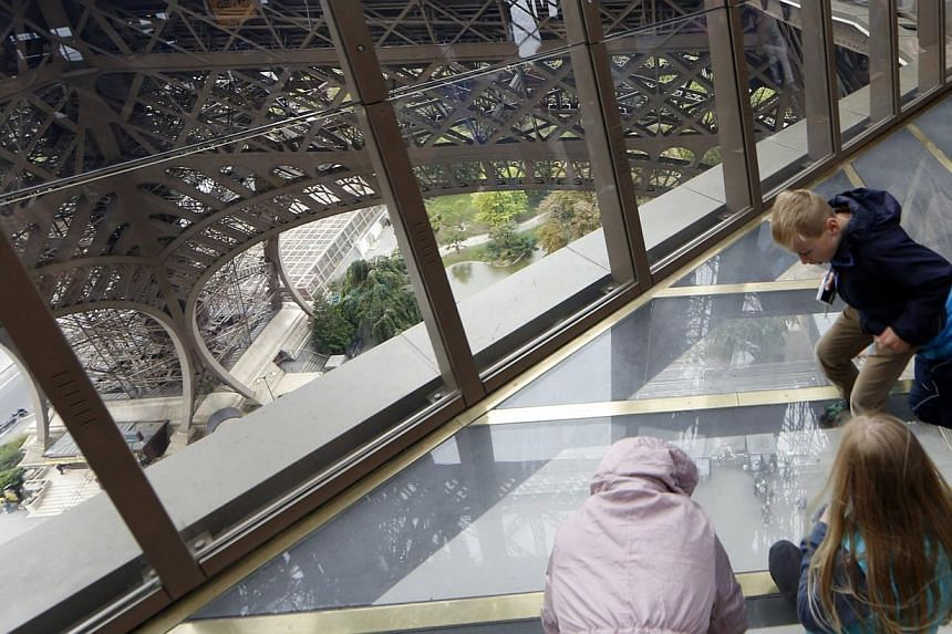 Visitors standing on the new glass floor. -- PHOTO: REUTERS