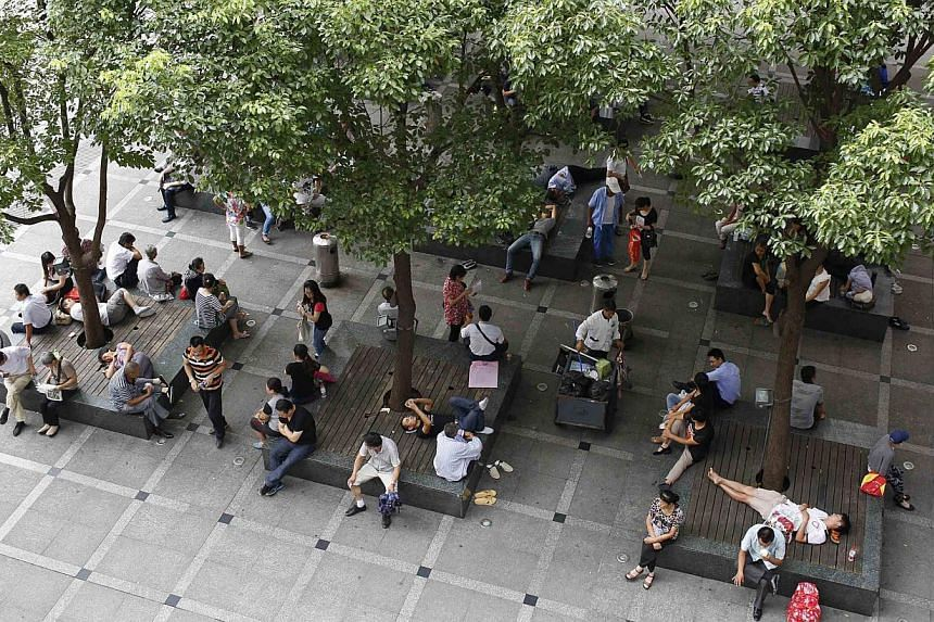 People rest under the trees outside a hospital in Shanghai, on Sept 1, 2014. -- FILE PHOTO: REUTERS