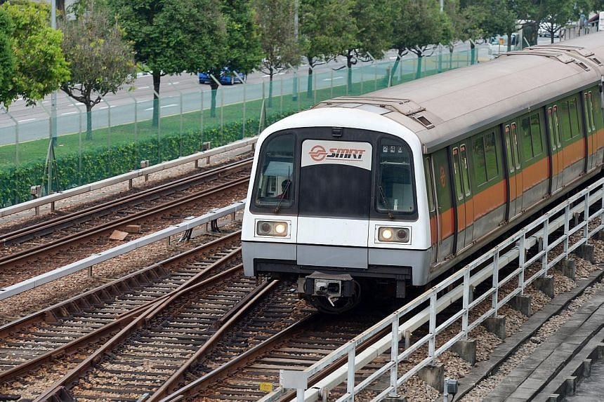 An MRT train travelling on the tracks along Ang Mo Kio Avenue 8.The overall waiting time on the North-South and East-West MRT lines during the peak is now 2.3 minutes, down from 2.5 in January. -- PHOTO: ST FILE