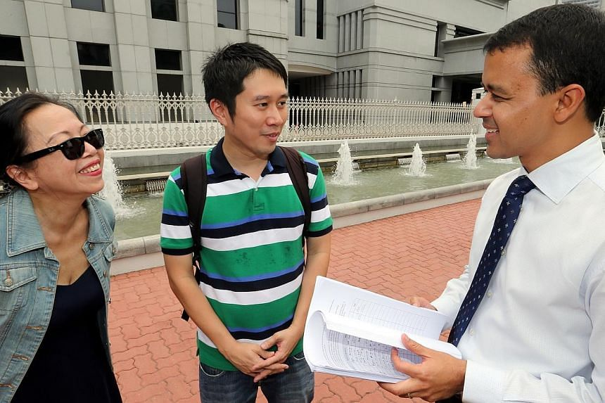 (From left) Ms Shelley Thio and Mr Jolovan Wham, from Stop Trafficking SG, deliver their petition to MP Christopher De Souza, outside Parliament House on Tuesday.-- ST PHOTO:WONG KWAI CHOW