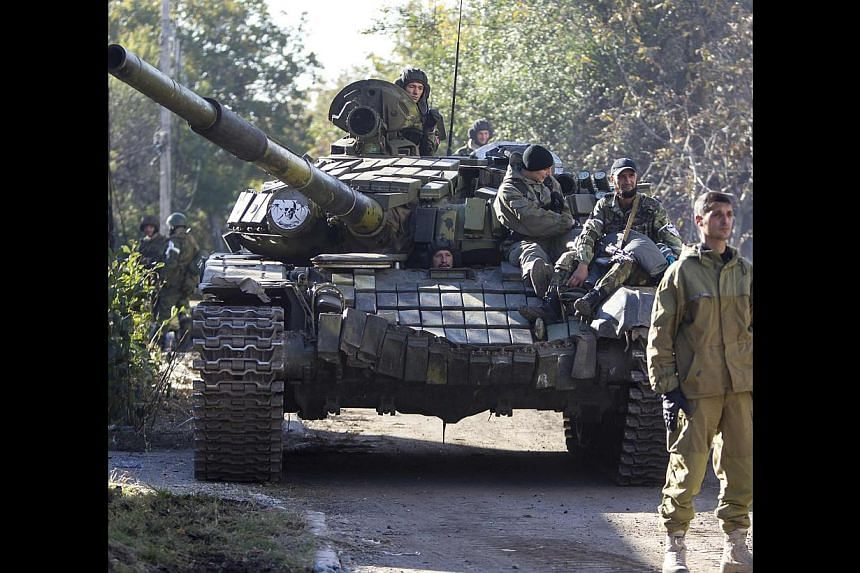 Pro-Russian rebels on a tank near the airport in Donetsk on Saturday. The best course of action for the US and Europe is to make it clear that territorial encroachment in Ukraine or elsewhere will be very costly.