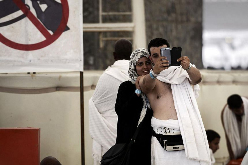 The trend of taking selfies has caught on at this year's haj. Key stages of the religious gathering, including the stoning of Satan (above) in Mina, near the holy city of Mecca, last Saturday have been recorded on mobile devices for posterity and for