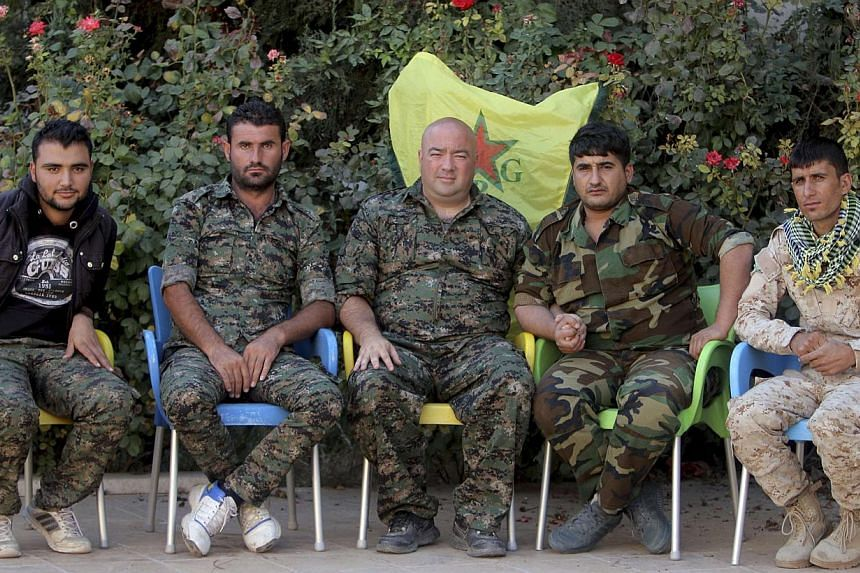Mr Brian Wilson (middle), who said he is a US citizen and a former soldier from Ohio, and who has joined the Kurdish People's Protection Units (YPG), sits with YPG members during an interview with Reuters in the north-east Syrian Kurdish city of Qami