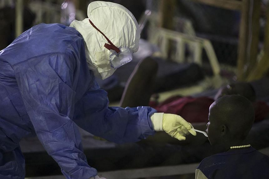 A health worker wearing protective equipment feeds a patient being treated for Ebola at the Island Clinic in Monrovia, on Sept 30, 2014. The first Ebola patient diagnosed in the United States is now receiving an experimental drug for the disease, a h