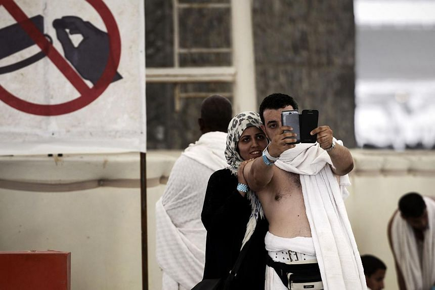 """Muslim pilgrims pose for a selfie during the """"Jamarat"""" ritual, the stoning of Satan, in Mina near the holy city of Mecca, on Oct 4, 2014. -- PHOTO: AFP"""