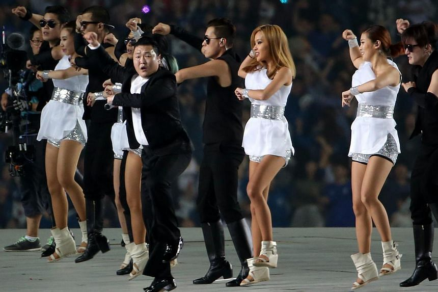 Popular South Korean pop star Psy performs his trademark Gangnam Style hit with his dancers, ensuring the Asian Games opening ceremony ends on a high at the Incheon Asiad Main Stadium, in incheon, South Korea on Sept 19, 2014. -- PHOTO: ST FILE