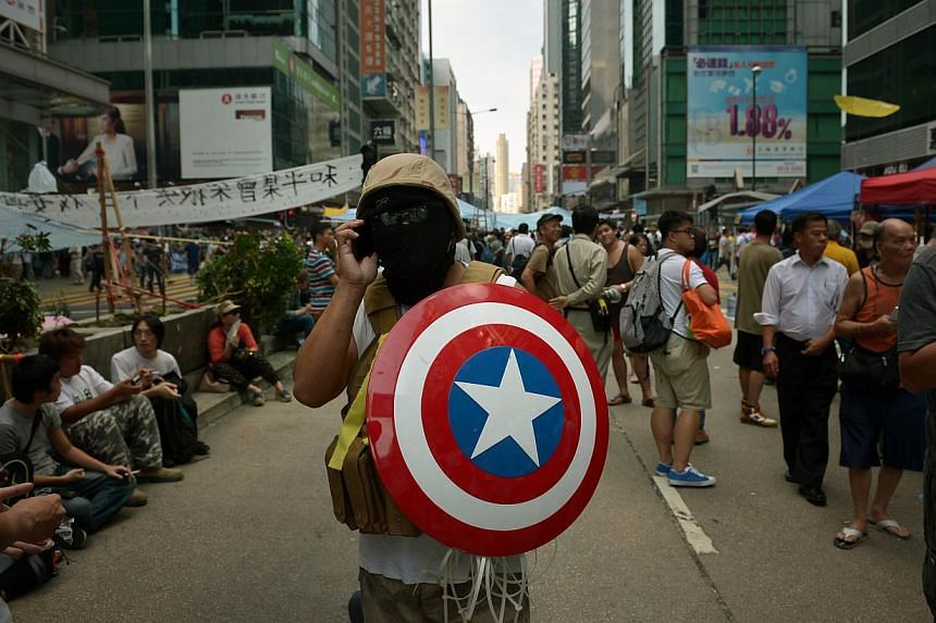 A protester holds a Captain America shield and wears army fatigues as he walks on the streets in Mong Kok in Kowloon on Oct 6, 2014. -- ST PHOTO: KUA CHEE SIONG