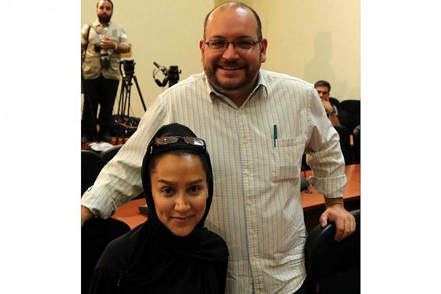 A file picture shows Iranian-American Washington Post correspondent Jason Rezaian and his Iranian wife Yeganeh Salehi posing while covering a press conference at Iran's Foreign Ministry in Tehran, on Sept 10, 2013. -- PHOTO: AFP