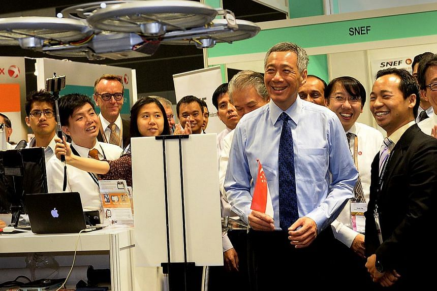 Prime Minister Lee Hsien Loong getting ademonstration of the flying robot waiter at the launch of National Productivity Month.-- ST PHOTO:JAMIE KOH